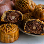 Ferrero Rocher Brownie Mooncakes cut in half with a teapot in the back