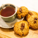 Walnut cookies on a wood chopping board with tea